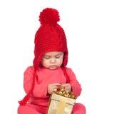Neonata con il cappello delle lane che osserva un regalo Fotografie Stock Libere da Diritti