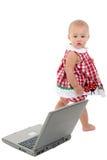 Neonata con il computer portatile sopra bianco. Fotografie Stock