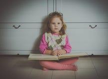 Neonata con il libro ed i vetri che si siedono sul pavimento Fotografie Stock Libere da Diritti