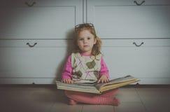 Neonata con il libro ed i vetri che si siedono sul pavimento Fotografia Stock