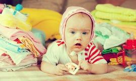 Neonata con il mucchio di baby& x27; usura di s Fotografie Stock