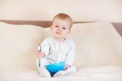 Neonata con la ciotola ed il cucchiaio in sua mano Fotografia Stock Libera da Diritti