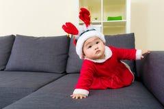Neonata con natale che si veste e che striscia sul sofà immagini stock libere da diritti