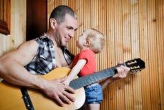 Neonata con suo padre dei pantaloni a vita bassa che gioca chitarra su fondo di legno Fotografie Stock Libere da Diritti
