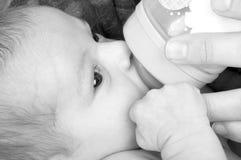 Neonata con un biberon. immagine stock