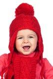 Neonata con un cappello divertente di colore rosso delle lane immagini stock