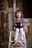 Neonata con un libro e una risata studio Immagini Stock