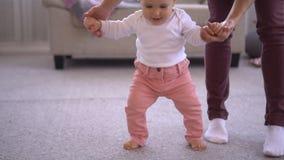 Neonata d'aiuto della madre per camminare e prendere il suo giocattolo stock footage