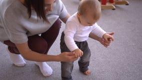 Neonata d'aiuto della madre per camminare e prendere il suo giocattolo video d archivio
