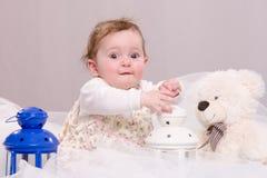 Neonata di sei mesi che gioca con i giocattoli sullo strato Immagini Stock