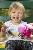 Neonata di un anno adorabile che si siede su un banco con una bambola i Fotografia Stock Libera da Diritti