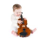 Neonata divertente che gioca con un grande violino Immagine Stock