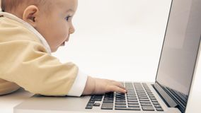 Neonata divertente che prova a utilizzare un computer portatile nel suo proprio modo video d archivio