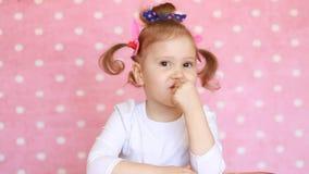 Neonata divertente dolce che esamina la macchina fotografica e sorridere Ritratto di un bambino sveglio su un primo piano rosa de stock footage