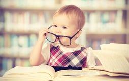 Neonata divertente in vetri che legge un libro in una biblioteca