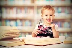 Neonata divertente in vetri che legge un libro in una biblioteca Immagini Stock