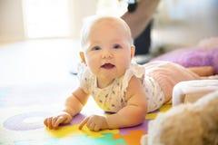 Neonata felice con gli occhi azzurri che giocano sul compagno del pavimento Immagini Stock Libere da Diritti