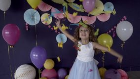 Neonata graziosa che getta i coriandoli luminosi e che celebra la sua festa di compleanno video d archivio
