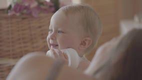 Neonata graziosa che gioca con la bottiglia che si siede sul letto vicino alla mamma a casa Bambino caucasico adorabile all'inter video d archivio