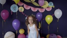 Neonata graziosa che salta sotto i coriandoli luminosi che celebrano la sua festa di compleanno stock footage