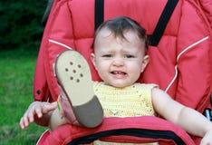 Neonata gridante che si siede in passeggiatore fotografia stock