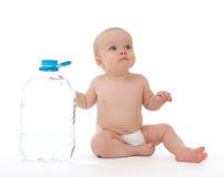 Neonata infantile del bambino che si siede con la grande bottiglia di acqua potabile Immagini Stock