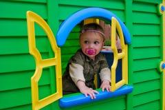 Neonata nella finestra del playhouse Fotografia Stock