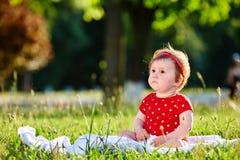 Neonata piacevole adorabile sveglia nella seduta sorridente del vestito dalla primavera rossa sotto l'albero Fotografie Stock Libere da Diritti