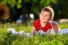 Neonata piacevole adorabile sveglia nella seduta sorridente del vestito dalla primavera rossa sotto l'albero Immagini Stock