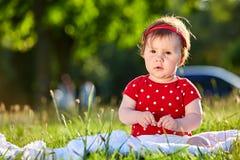 Neonata piacevole adorabile sveglia nella seduta sorridente del vestito dalla primavera rossa sotto l'albero Immagine Stock Libera da Diritti