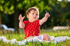 Neonata piacevole adorabile sveglia nella seduta sorridente del vestito dalla primavera rossa sotto l'albero Fotografia Stock Libera da Diritti