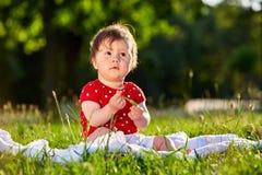 Neonata piacevole adorabile sveglia nella seduta sorridente del vestito dalla primavera rossa sotto l'albero Fotografia Stock