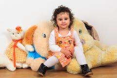 Neonata riccia che si siede su un giocattolo del cane della peluche Fotografia Stock