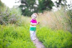 Neonata riccia sveglia che cammina in un parco Fotografia Stock