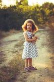 Neonata riccia sveglia di estate o di tempo di caduta Ragazza dolce del bambino in un vestito con la stampa di zigzag in un parco Immagine Stock