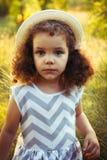 Neonata riccia sveglia di estate o di tempo di caduta Ragazza dolce del bambino in un vestito con la stampa di zigzag in un parco Immagini Stock Libere da Diritti