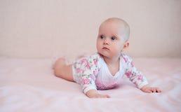 Neonata seduta su sul letto Immagine Stock