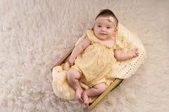 Neonata sorridente che porta un pagliaccetto giallo fotografie stock libere da diritti