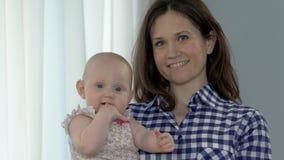 Neonata sorridente della tenuta della donna, bambino che succhia dito, maternità felice, armonia video d archivio