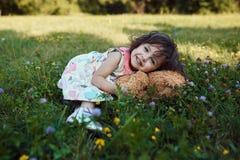 Neonata sorridente sveglia che abbraccia il giocattolo molle dell'orso Fotografie Stock