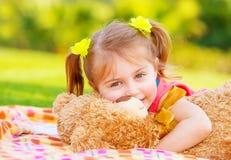 Bambina che abbraccia giocattolo molle Immagine Stock