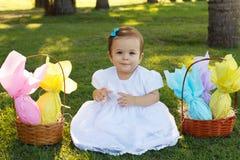Neonata sorridente sveglia con il canestro con le uova di cioccolato per Easte Immagine Stock Libera da Diritti