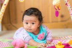 Neonata sul pavimento con i giocattoli Immagine Stock