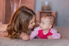 Neonata sveglia che celebra insieme giorno di nascita vicino ai palloni rossi Scena adorabile del bambino sul divano del sofà con Immagine Stock