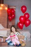 Neonata sveglia che celebra insieme giorno di nascita vicino ai palloni rossi Scena adorabile del bambino sul divano del sofà con Fotografie Stock