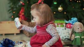 Neonata sveglia che dà i regali di Natale ai suoi genitori e che si siede vicino all'albero di Natale Primo piano stock footage