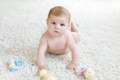 Neonata sveglia che gioca con il giocattolo d'annata pastello variopinto di crepitio Fotografia Stock Libera da Diritti