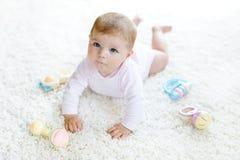 Neonata sveglia che gioca con il giocattolo d'annata pastello variopinto di crepitio Immagine Stock