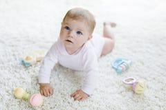 Neonata sveglia che gioca con il giocattolo d'annata pastello variopinto di crepitio Immagine Stock Libera da Diritti