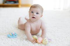 Neonata sveglia che gioca con il giocattolo d'annata pastello variopinto di crepitio Fotografie Stock Libere da Diritti
